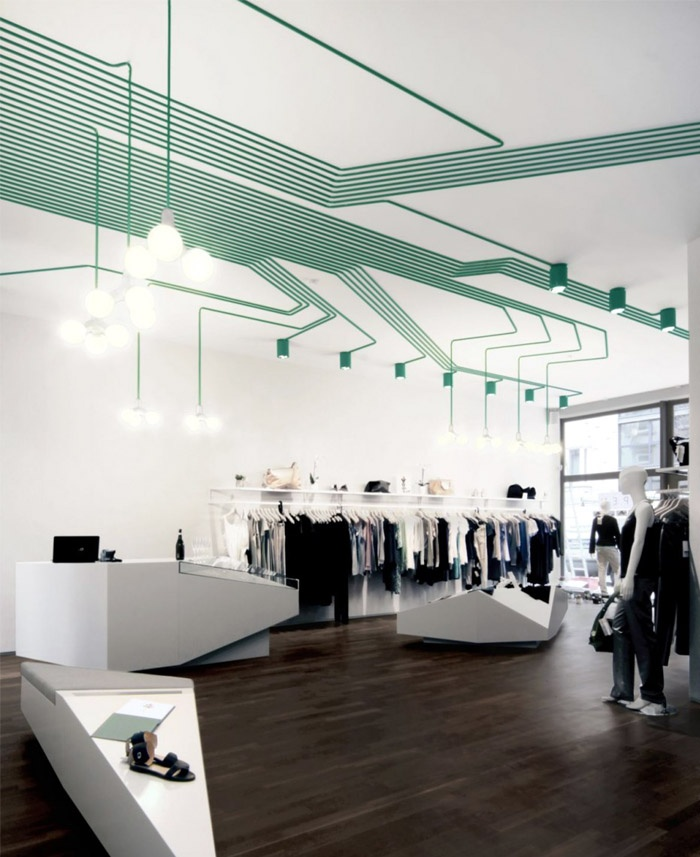 """Instead of hiding the cables of the light installation behind a drywall ceiling, KINZO displays them openly to create a """"computer chip"""" pattern that lures the visitor into the centre of the store. The ceiling-mounted lamps were also designed by KINZO and specially manufactured for this project by idee.design.licht., a German specialist in bespoke lighting solutions."""
