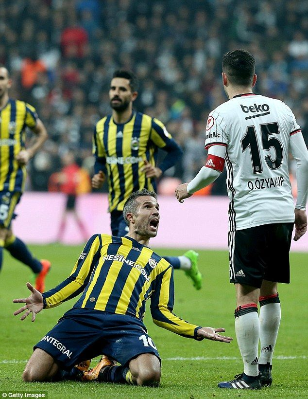 Robin van Persie celebrates with a knee slide in front of his old Arsenal team-mate Oguzhan Ozyakup after scoring Fenerbahce's winner against Besiktas in the Turkish Cup