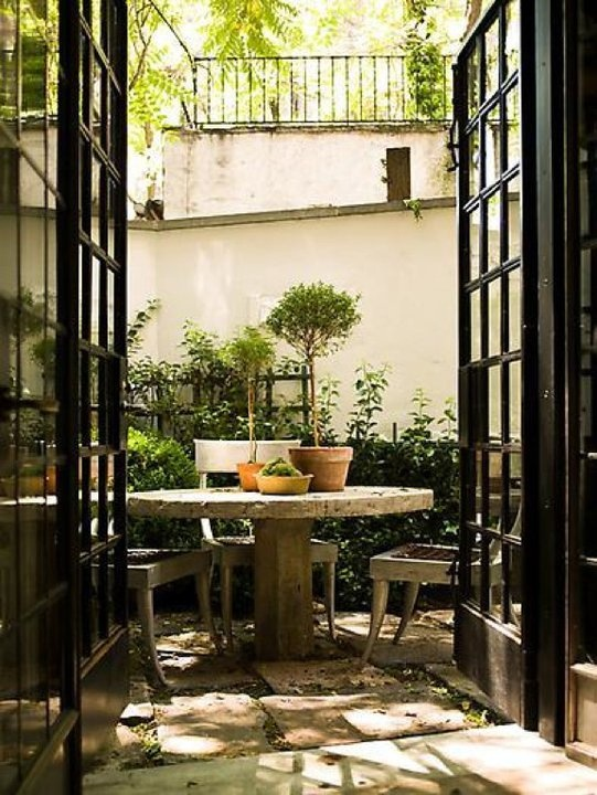 glass roof courtyard connected to greenhouse.. entrance off home in multiple rooms black French doors and windows