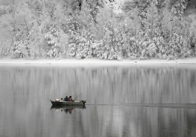 A man fishes in a motorboat on the Yenisei River, with the air temperature at about minus 15 degrees Celsius (5 degrees Fahrenheit) outside Russia's Siberian city of Krasnoyarsk December 28, 2012.