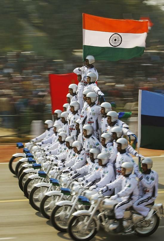 Indian army soldiers perform motorcycle stunts as they carry the Indian flag at the parade in New Delhi.