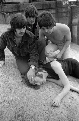 A shirtless Paul McCartney joins Ringo Starr and George Harrison as they crouch over John Lennon playing dead while  at Wapping Pier Head in London.