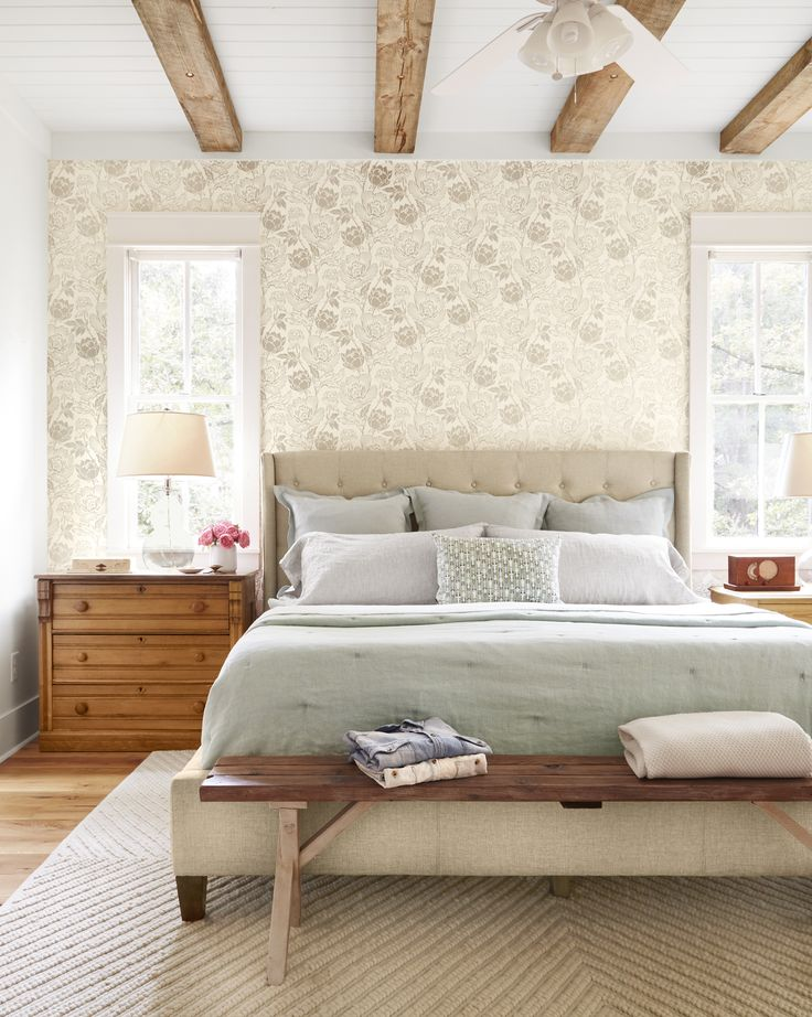 A sophisticated gray-brown floral wallpaper  mimics the hue of the weathered ceiling beams and offers a feminine (but not frilly) foil to the master bedroom's rustic elements. Formerly a park bench, the piece at the foot of the tufted bed features someone's nearly faded, hand-carved initials.