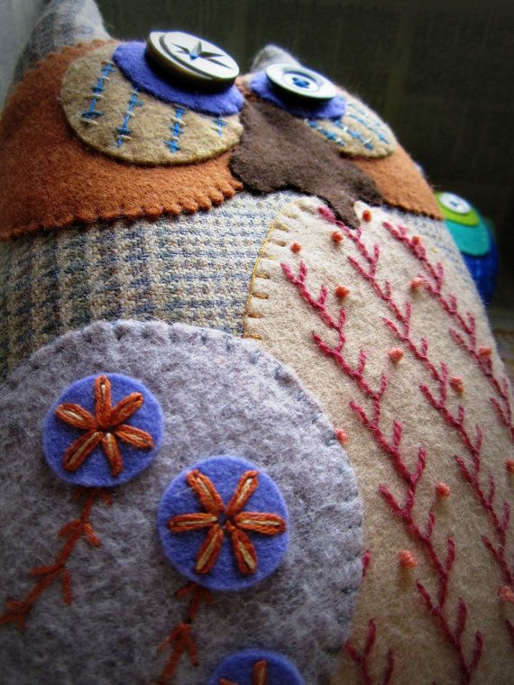A Murgatroyd & Bean Original Design    Meet the Rocca Owls, a tribe of shy, yet flamboyant, winged creatures. Recognisable by their flared legs and love of embellishment and colour. They have a penchant for Glam Rock music and highly decorated canal boats. They are covered in hand embroidery, each Rocca is a one-off.    This Rocca is made from a sporting, checked wool tweed, shot through with a hint of smokey blue. His large eyes & wings are made from wool & wool mix felt with a c...