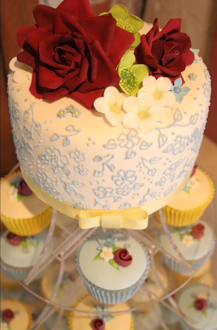 Blue and yellow meadow inspired cupcakes and top tier. All handmade sugar flower arrangements and piped lace detail.