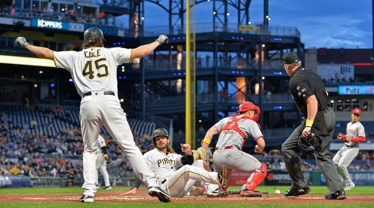 YOU ARE SAFE!     Gerrit Cole of the Pirates reacts as John Jaso slides safely past Stuart Turner of the Reds to score on Sept. 1 in Pittsburgh. The Reds won 7-3.
