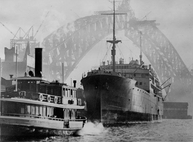 On a misty day in 1930, high over the ships in the harbour, the two halves of the Harbour Bridge are almost ready to be joined.