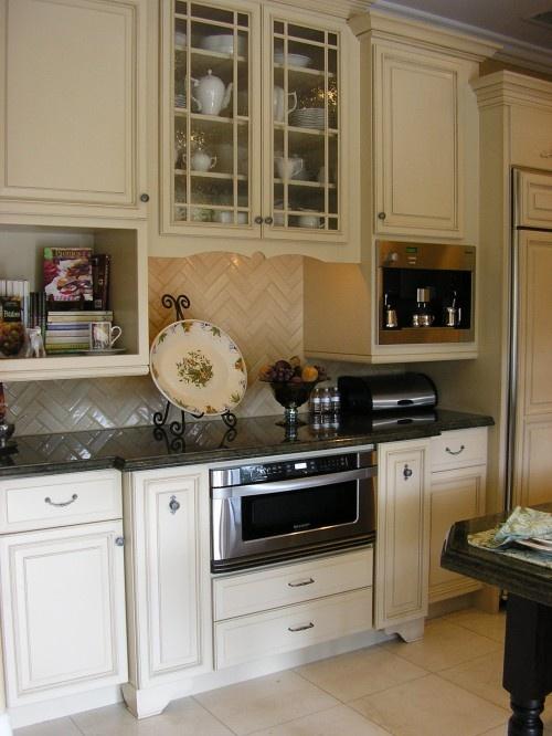 So interesting... besides the awesome herringbone tile backsplash.. white lower cabinets, cream upper.. ??