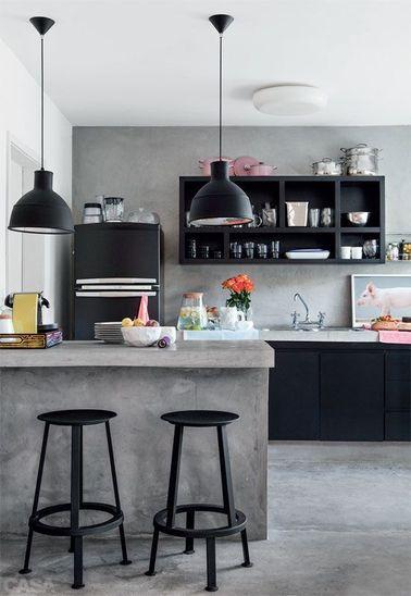 Une cuisine ouverte noire et grise avec comptoir en béton ciré