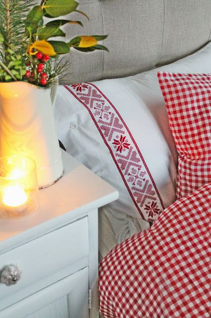 White linens trimmed in red scandinavian ribbon with red gingham duvet