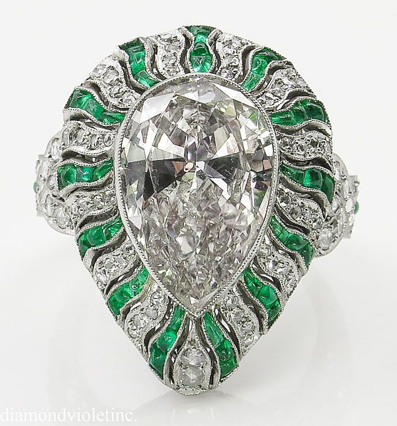 A Breathtaking Vintage PLATINUM (stamped) Diamond and Green Emerald Anniversary ring. The Bezel Set Pear Shaped Diamond is estimated 4.72CT with measurements of 15.30x10.10x5.20mm; GEMOLOGIC Certified in L-M color SI2 clarity (Warm slightly golden tint, eye clear). Beautiful Large Pear