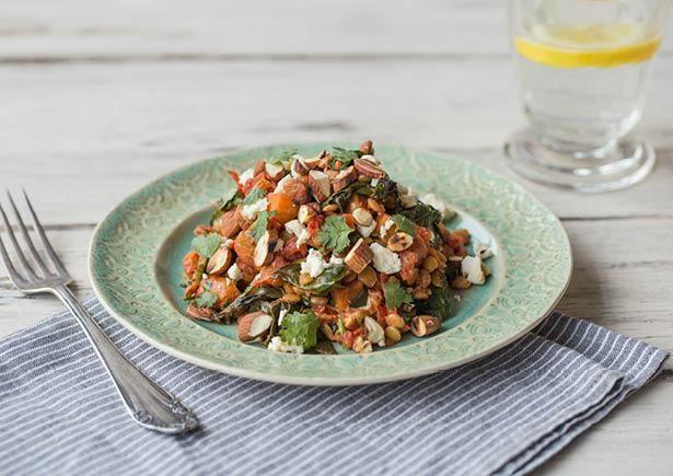 Groene linzen met spinazie, bataat, feta en amandelen Gezonde winterse maaltijd gegarneerd met verse koriander