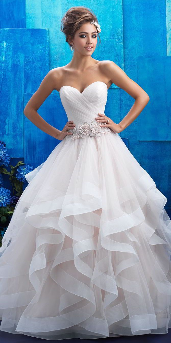 The sheer ruffles adorning this gown's ballgown skirt are both fluid and structured, topped with a floral belt.
