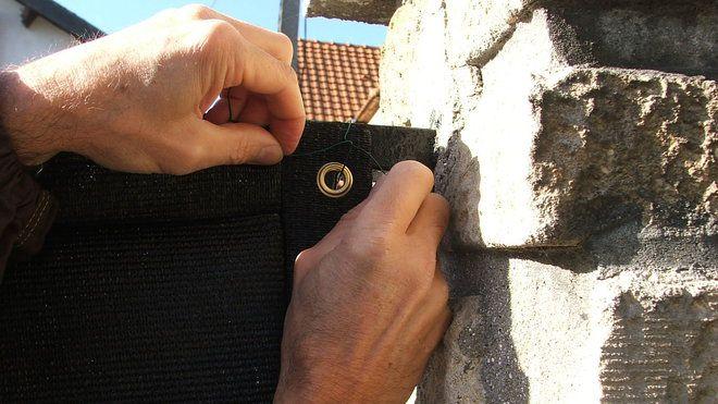 Brise vue portail par étapes ! Etape 5 : La fixation s'effectue en passant le morceau de fil souple de grillage par l'œillet fixé sur le cadre en métal ; bien tendre le fil, en serrant et en entourant les extrémités du fil souple.