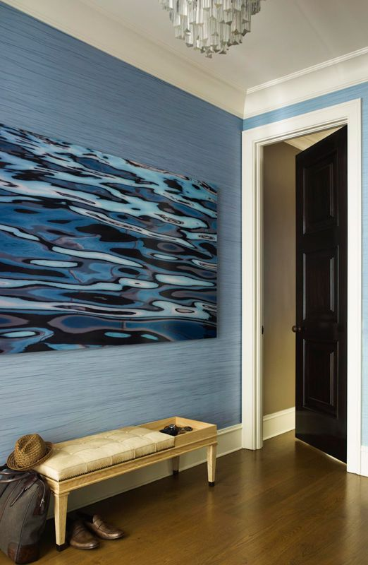 An azure blue fabric wall covering by maya romanoff lends texture and vibrancy in this foyer
