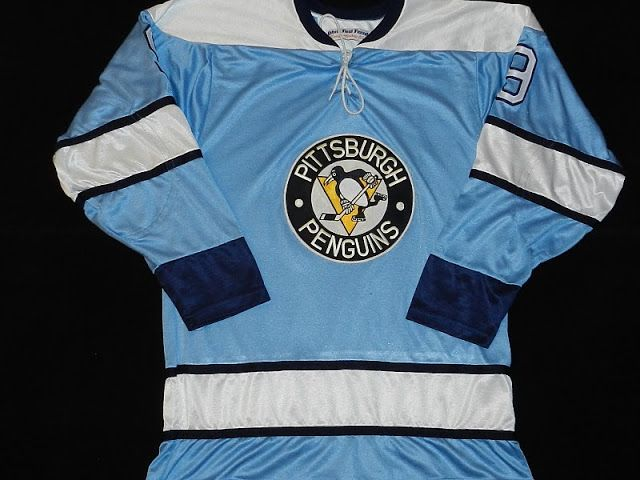 FOR THE 1968-69 SEASON, PITTSBURGH CHANGED TO A JERSEY WITH ITS PRIMARY LOGO ON THE FRONT; MODIFIED ITS STRIPE-PATTERN, AND ADDED A SHOULDER YOKE (ABOVE). THIS DESIGN REMAINED IN PLACE FOR THREE SEASONS, THROUGH 1970-71. FOR THE INITIAL OUTDOOR WINTER CLASSIC (JAN. 1, 2008, PITTSBURGH AT BUFFALO - RALPH WILSON STADIUM), THE PENGUINS RE-INTRODUCED THE DESIGN (BELOW), THOUGH THE PREDOMINANT COLOR WASN'T AS TRUE AS THE LIGHT-BLUE WORN BY THE CLUB IN ITS EARLY YEARS. STILL, IT SOLD TREMENDOUSLY…