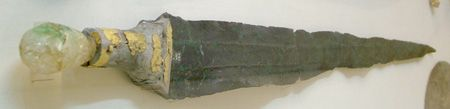 link between the Minoan triangular small swords or daggers and the long A Type sword can be represented by the specimen found in Mallia Crete dated around 1700 BC. This sword shows a large and long blade with a large and flat midrib