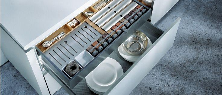 Deze lichte keuken van Next125 heeft witte, greeploze kastjes en een eveneens licht aanrechtblad.
