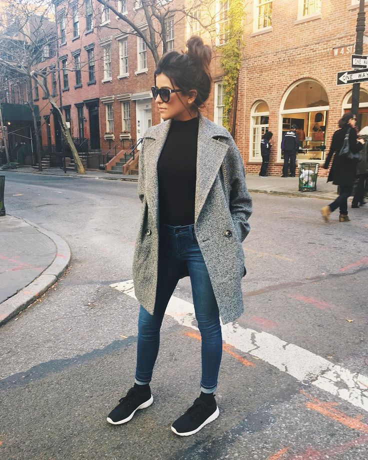 Gray coat. Black high collar shirt. Medium blue skinny jeans. Black lace-up shoes. Sunglasses.