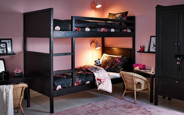 A black-brown bunk bed with quilt covers and pillowcases in black/pink with unicorn pattern