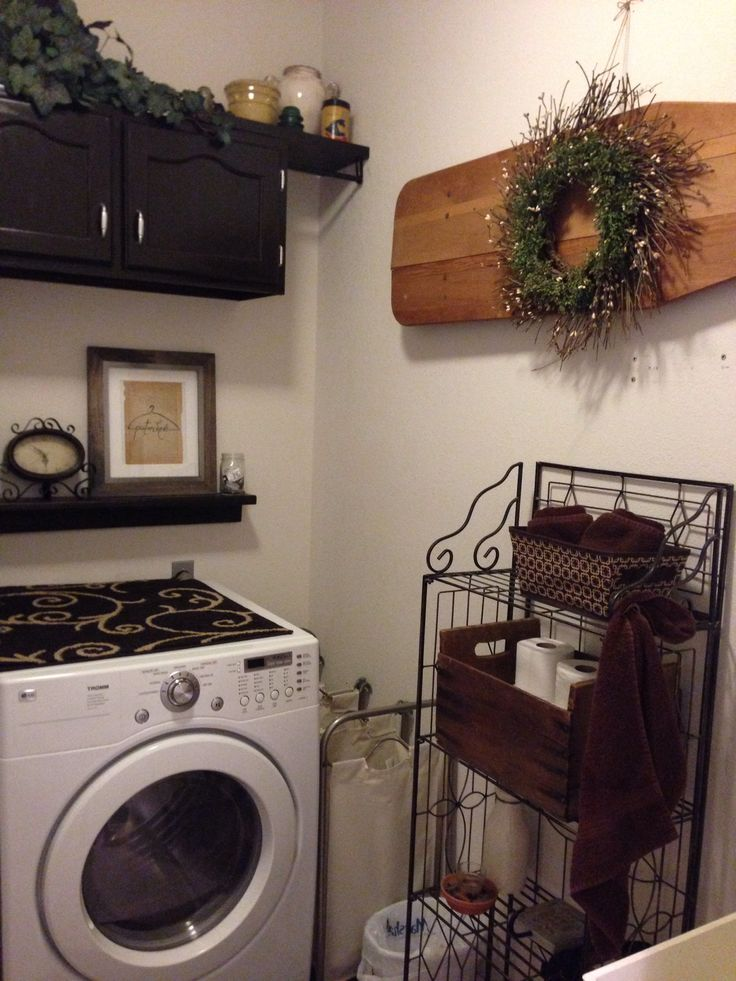 My remodeled laundry room. Added much needed storage with refurbished used cabinets, made a shelf from pallet wood, used an old box for storage and hung an antique ironing board for cute!