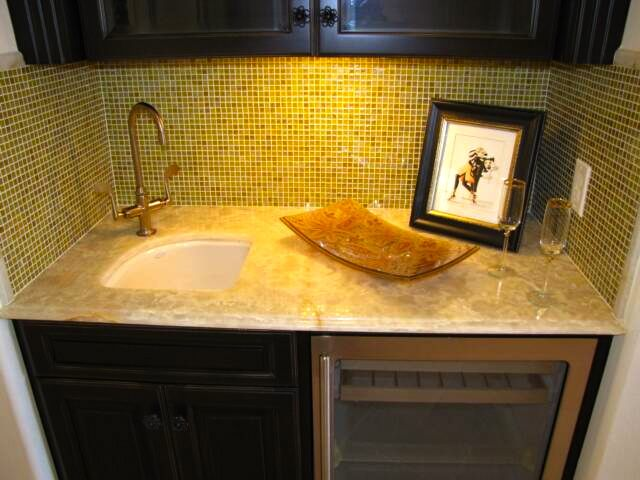 A Small Wet Bar Area With Granite Countertop And Tiled