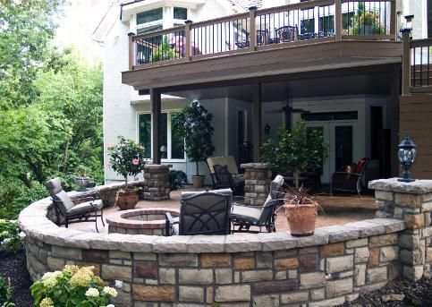 Love this combo of small upper deck, covered lower space and rock look walls/ patio ! EverGrain - Weathered Wood Deck with powder-coated aluminum under deck ceiling system, Stone veneered sitting walls, Stamped/Stained/Sealed concrete patio, Moonlight Decks post lights, Wall lighting, retaining wall, landscaping and a natural stone patio in Leawood, KS. #decksandpatios