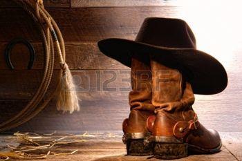 cowboy WESTERN: American West cowboy de rodéo traditionnel chapeau de feutre noir reposant sur des bottes de travail en cuir usés roper ranch avec d'authentiques occidentaux éperons d'équitation et lasso lasso dans une grange en bois ranch millésime