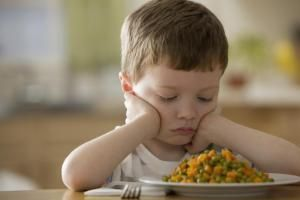 Unhappy Caucasian boy looking at dinner. - Blend Images - KidStock/Brand X Pictures/Getty Images