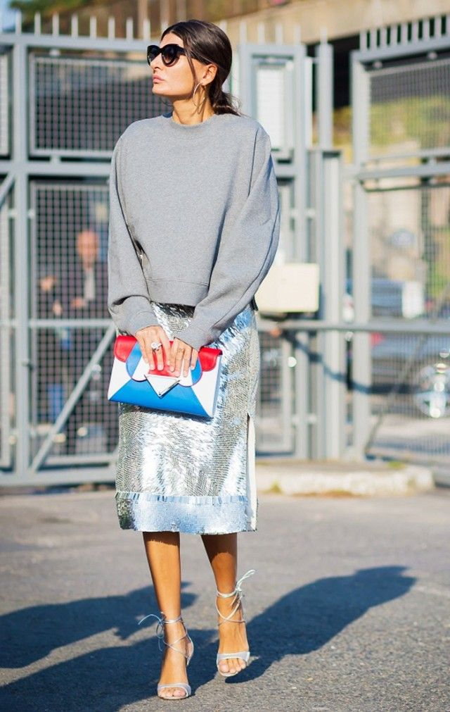 Giovanna Battaglia wears a gray sweatshirt, silver sequin skirt, lace-up heels, and a playful clutch