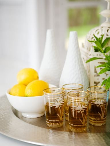 A punch of yellow with a bowl of lemons. Love the vintage palm tree shot glasses. A bar with personality!