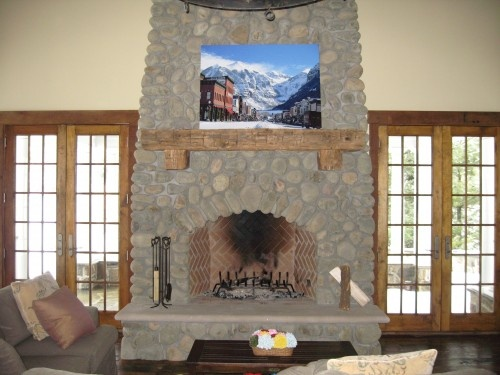 a beautiful stone fireplace complete with the perfect mantel shelf made of timber