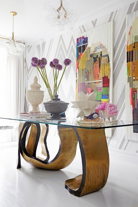 Eclectic and modern entryway with glass table styled with structural flowers, urns, and sculptures