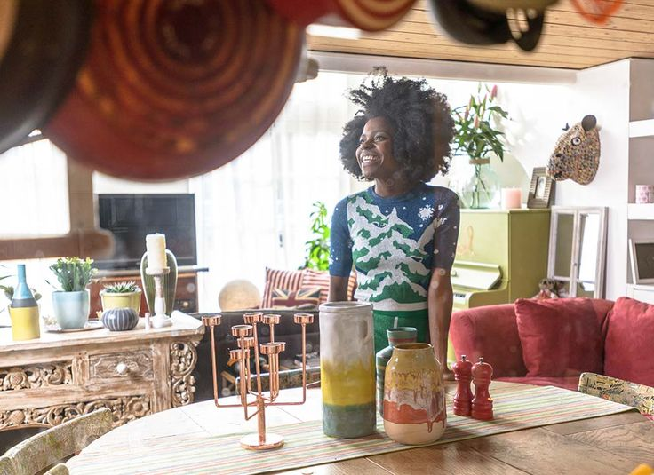 Freddie Harrel standing in her living room, surrounded by some of her prized possessions.