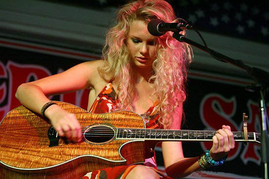 A young female with curly blond hair faces down at an acoustic guitar made of koa wood while a large microphone is placed close to her. She is wearing patterned, red dress.
