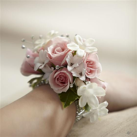 Pure Grace Wrist Corsage. We've gone for a look that's classically feminine and graceful with this exquisite wrist corsage. Fresh roses in softest pink, dainty white stephanotis and delicate hyacinth flowers mingle with sparkling rhinestones to create a very beautiful adornment.