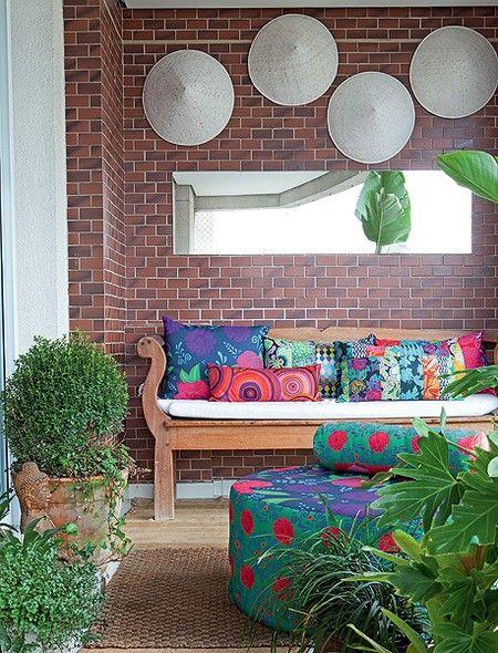 A base neutra da varanda ganhou almofadas e banco coloridíssimos, com estampas da designer Ana Morelli. Repare como todas têm uma mistura de azul e vermelho, em diferentes tons
