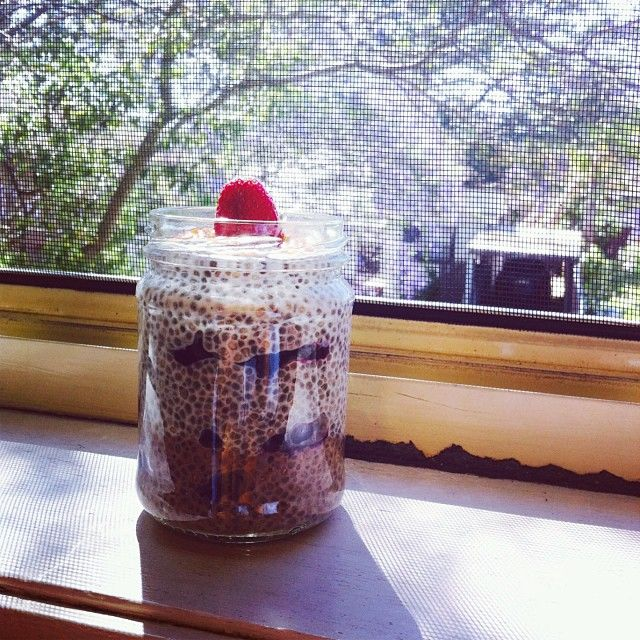 A mini chia pud with blueberries, topped with golden flaxseeds and a homegrown strawberry. Base layer is cacao, while the top is vanilla.