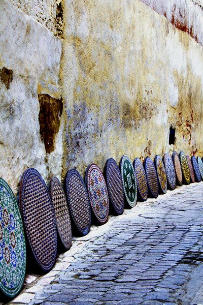 Ceramic table tops lining a wall in Fez, Morocco. Photographer could not be traced