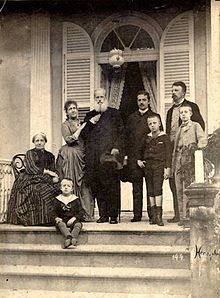 Last picture of the Imperial Family in Brazil, 1889 - Photograph of a group of people assembled on a columned porch at the top of a flight of steps, with one older lady seated, one younger lady leaning on the arm of an older bearded man, two younger men and three small boys