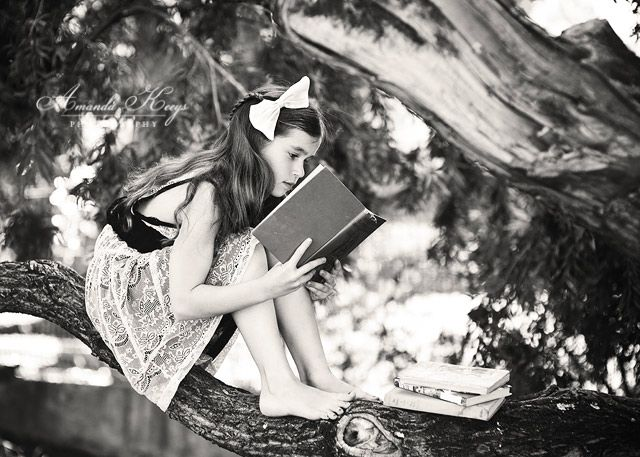 Girl sitting in a tree reading