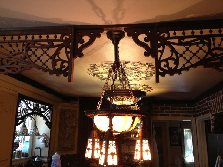 Victorian room divider and slag glass lamp separating the kitchen and the nook