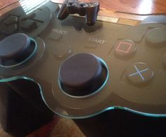 """Power up your game room with the addition of the Playstation controller coffee table. This beautiful hand sculpted wooden table is designed to resemble a PS3 controller right down to the smallest detail and comes with a 1/2"""" glass surface."""