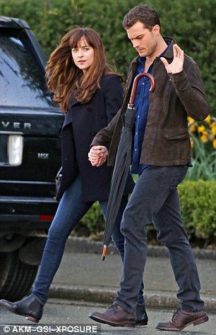 Ready, set, action: The 26-year-old actress, who plays Anastasia Steele, bundled up in jeans and a navy trench coat while Jamie - Mr. Christian Grey himself - wore a blue top, black jeans and a suede coat while on set