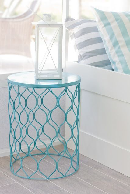 Turn a metal wastebasket into a side table. Genius, cheap and you can always turn it back over if you need an extra one~