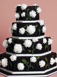Chocolate Dream - This four-tiered cake is iced with chocolate fondant, trimmed with white fondant ribbon, and decorated with clusters of white sugar flowers. ~Cake by Elisa Strauss, Confetti Cakes~