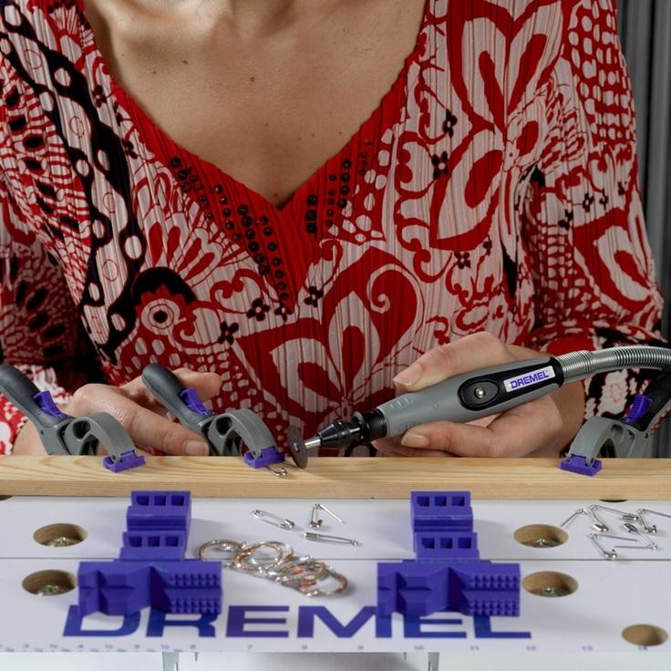 Pasul 2    Legaţi cercurile din sârmă cu inele de legătură pentru bijuterii şi adăugaţi sistemul de închidere. Puneţi o bucată de lemn pe staţia de lucru de la Dremel şi fixaţi un ac de siguranţă de bucata de lemn. Folosiţi Dremel 300 la care ataşaţi axul flexibil 225 pentru a tăia cu precizie. Utilizaţi discurile de debitare, dispozitivul de prindere universală şi mandrina pentru a tăia vârful acului de siguranţă.