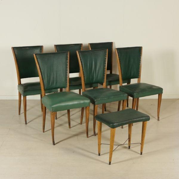 Gruppo di sei sedie e uno sgabello; legno di faggio, imbottitura a molle, puntali in ottone, rivestimento in similpelle. Buone condizioni; presentano piccoli segni di usura.