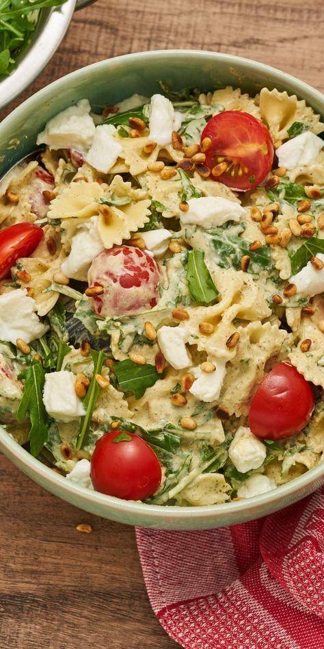 """Unser Nudelsalat """"Rucola"""" ist dein perfekter Begleiter zur nächsten Grillparty und jeder anderen Veranstaltung. Du wirst dich vor Komplimenten kaum retten können, so lecker ist er! Tomaten, Mozzarella und Basilikum-Pesto sorgen für den perfekten Geschmack."""