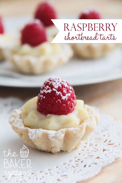 Raspberry shortbread tarts from The Baker Upstairs. A delicious sweet cookie crust filled with luscious custard and topped with fresh fruit. An elegant dessert that is sure to impress! www.thebakerupstairs.com